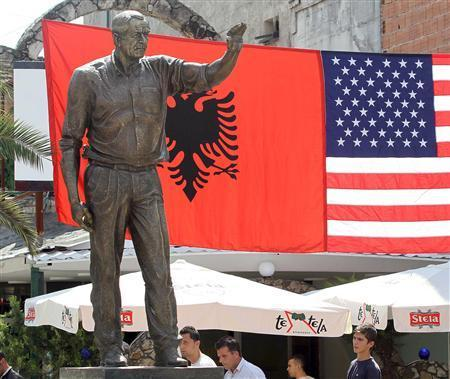 People walk near a statue of former U.S. President George W. Bush unveiled in the centre of the town of Fushe Kruje